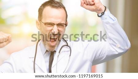 Doctor senior man, medical professional happy and excited celebrating victory expressing big success, power, energy and positive emotions. Celebrates new job joyful #1197169015