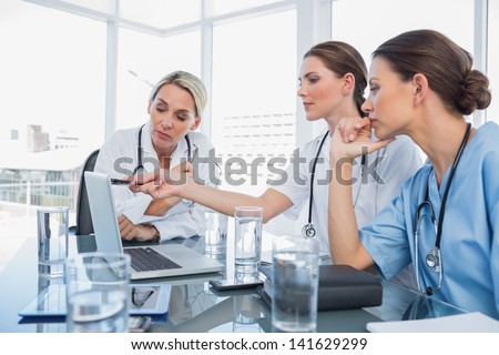 Doctor showing something on a laptop to her colleagues during a meeting room