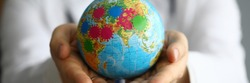 Doctor shows globe with coronavirus, world pandemic. Coronavirus is global problem in world. Temporary ban on entry into countries. Crisis, unlimited by territory continent and requiring cooperation