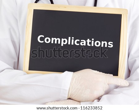 Doctor shows information on blackboard: complications - stock photo