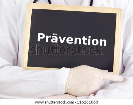 Doctor shows information on blackboard: prevention - stock photo