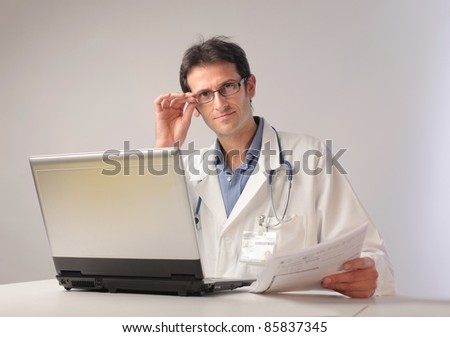Doctor sitting at a desk in front of a laptop - stock photo