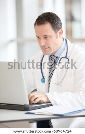 Doctor sitting at his desk with laptop computer