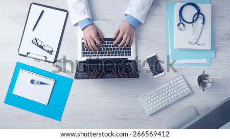 Doctor sitting at office desk and working on his laptop with medical equipment all around, top view