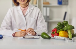 Doctor sitting at table with fresh raw fruit and vegetables and individual weight loss and slimming plan. Cropped female dietitian or nutritionist recommends sticking to diet and eating healthy food