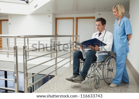 Doctor sitting in wheelchair examining notes with nurse in hospital corridor