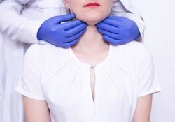 Doctor specialist diagnoses palpation on the throat of the caucasian girl for the presence of enlarged lymph nodes and tumors, adenoids