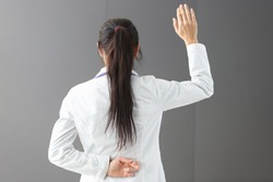 Doctor standing with crossed fingers behind his back. Medical secrecy concept