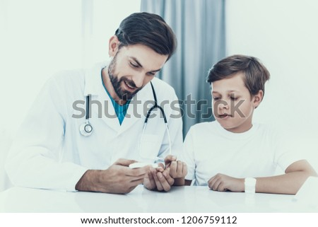Doctor Taking Blood Sample from Boy's Finger. Diabetes Concept. Sugar in Blood. Healthcare Concept. Young Man in Uniform. White Coat. Medical Equipment. Boy in Clinic. Glucometer in Hand.
