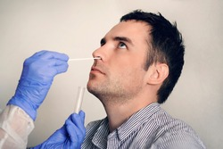 doctor taking nasal mucus test sample from male nose performing respiratory virus testing procedure. Checking the nasal cavity in the ENT. PCR polymerase chain reaction