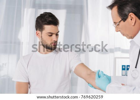 doctor taking patient blood for test in medical gloves
