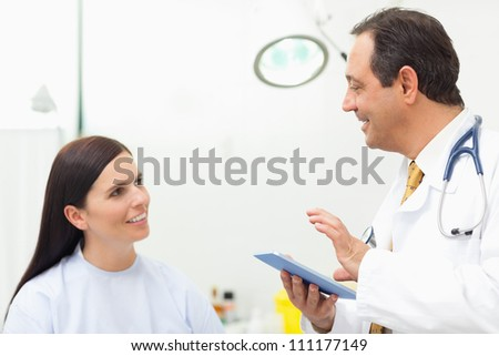Doctor talking to a patient while holding a tablet tactile in an examination room