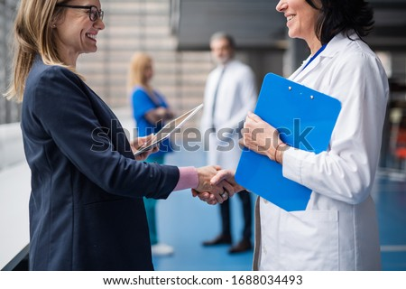Doctor talking to pharmaceutical sales representative, shaking hands.