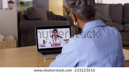 Doctor talking to Senior African woman patient over webcam