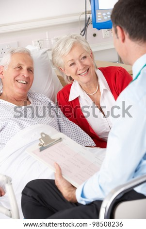 Doctor talking to senior couple on UK Hospital ward - stock photo