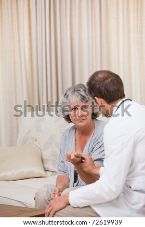 Doctor talking with his patient at home - stock photo