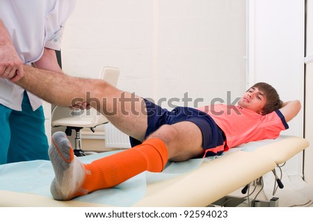 Doctor testing a knee for stability of injured football player in clinic