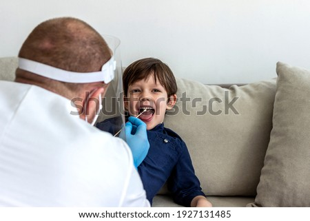 Doctor testing child for the coronavirus at home. Boy having a test swab taken by male doctor at home. COVID-19 home test kit. Specialist holding cotton swab and test tube ready to collect DNA. ストックフォト ©