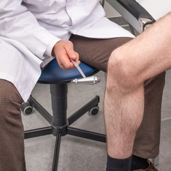Doctor testing the patellar reflex with a reflex hammer