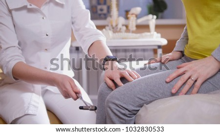 Doctor the neurologist examines the patient taps with a hammer on the knee, close up