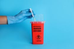 Doctor throwing used syringe into sharps container on light blue background, closeup