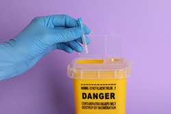 Doctor throwing used syringe needle into sharps container on violet background, closeup