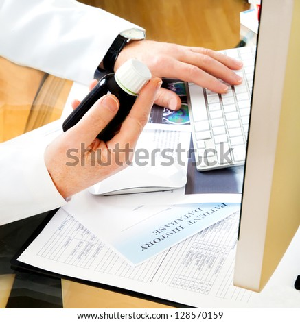 Doctor using a computer to prepare an online prescription or writing patient notes from a medical examination