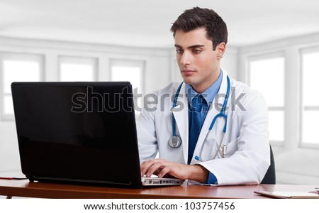 Doctor using a laptop computer on his desk