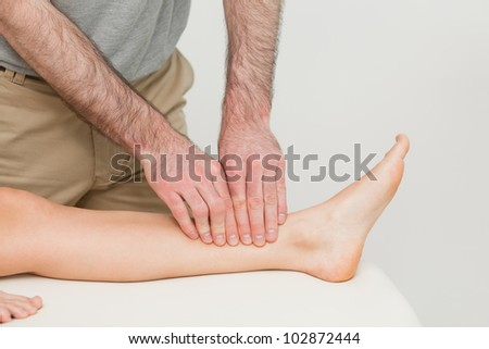 Doctor using his fingertips to massage a calf in a room