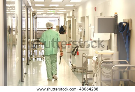Doctor using scrubs walking at the hospital corridor