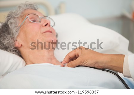 Doctor using stethoscope on elderly female patient in hospital bed
