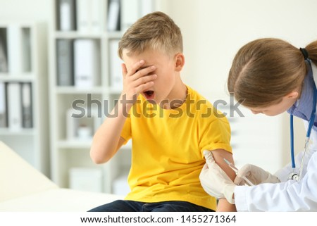 Doctor vaccinating little boy in clinic #1455271364