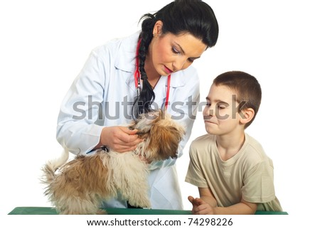 Doctor vet checking puppy ears and the child looking with admiration over white background