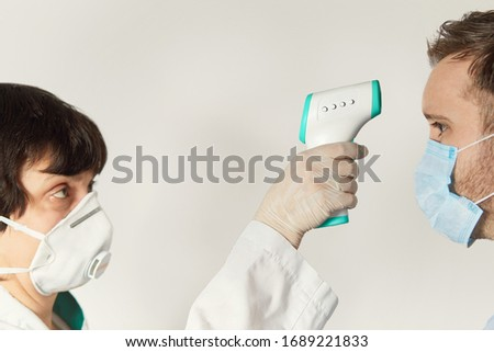 Doctor wearing a respirator N95 mask to use infrared forehead thermometer  to check body temperature for virus symptoms.  Respiratory diseases such as flu, coronavirus. Epidemic  outbreak