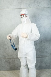 doctor wearing covid PPE suit uniform, face shield, gloves and FFP stands with phonendoscope