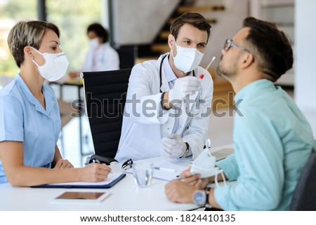Doctor wearing protective face mask and using cotton swab while doing PCR test of a patient during coronavirus pandemic.