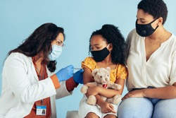 Doctor wearing protective face mask, gloves and shield giving vaccine in the arm of girl in mask. Small girl holding her teddybear getting covid-19 vaccine from a pediatrician.