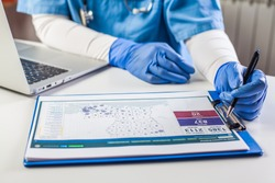 Doctor wearing protective gloves working on laptop computer,analyzing Coronavirus info data,COVID-19 response case info,U.S. state rank cases per capita,percent infected info and population numbers