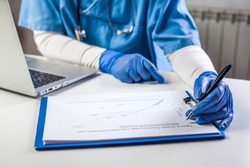 Doctor wearing protective gloves working on laptop computer,analyzing COVID-19 info data chart,SARS-CoV-2 global pandemic outbreak crisis,stats showing growth trajectory of Coronavirus patient cases