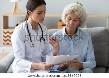 Doctor wearing uniform with stethoscope reading and holding documents, consulting older woman about checkup result, sitting on couch, mature patient listening to physician explaining prescription