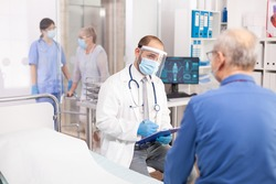 Doctor wearing visor as safety precaution in the course of consultation of senior man. Physician practitioner in the course of private modern clinic appointment during coronavirus pandemic.