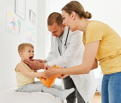 Doctor with a little boy and his mother or nurse in doctor's office in clinic