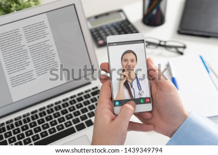 Doctor with a stethoscope on the smartphone screen. Telemedicine or telehealth concept.