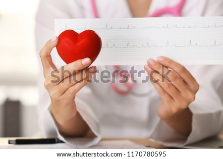 Doctor with cardiogram and red heart in clinic, closeup #1170780595
