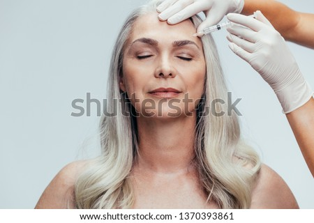 Doctor with gloves injecting with an needle into temple of the senior woman against grey background. Woman getting anti aging injection on her face to reduce wrinkles. #1370393861