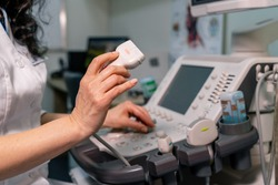 Doctor with professional equipment. Ultrasound scanner in doctor`s hands. Diagnostics. Sonography