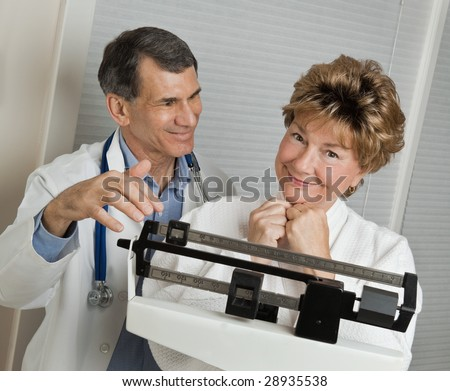 Doctor with smiling woman who has reached her target weight on medical scale in doctor's office.