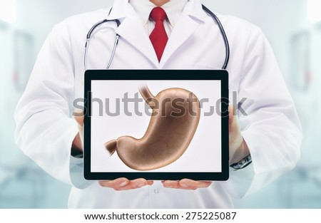 Doctor with stethoscope in a hospital. Stomach on the tablet. High resolution.