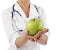 Doctor (woman) holding green apple with copy space on blue