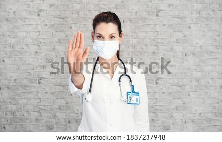 Doctor woman makes stopping hand gesture. Girl Doctor wearing protection face mask against covid-19. Banner panorama medical staff preventive gear about coronavirus. Woman in medical mask stops covid Stock fotó ©